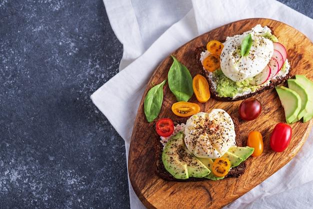 Bovenaanzicht vegetarische toast met gepocheerde eieren, kwark, avocado, spinazie, kerstomaatjes op houten bord op grijze achtergrond