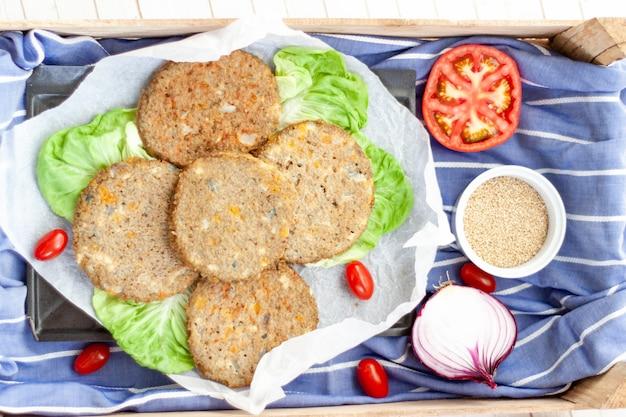 Bovenaanzicht veggie quinoa burger met tomaat, kerstomaatjes, ui, komkommer, sla