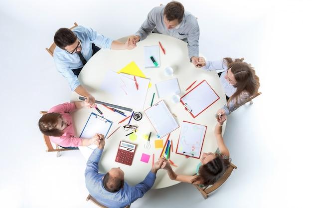 Bovenaanzicht. verenigde handen van commercieel team op werkruimteachtergrond