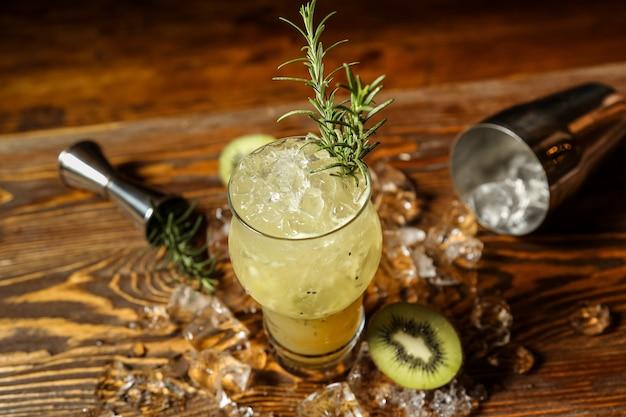 Bovenaanzicht verfrissende cocktail met rozemarijn en kiwi op ijs op tafel