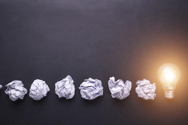 Bovenaanzicht verfrommeld wit papier en gloeilampen op zwarte stenen bord