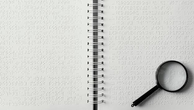 Bovenaanzicht vergrootglas op braille-notitieblok