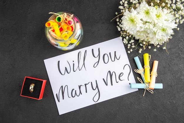 Bovenaanzicht verlovingsring in doos bloemboeket scroll wenspapieren in pot wil je met me trouwen geschreven op papier op donkere achtergrond