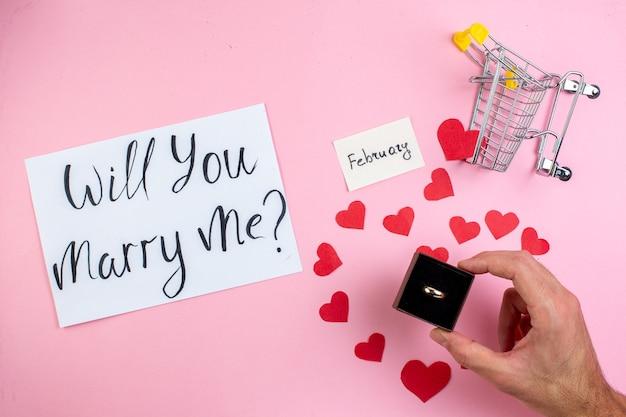 Bovenaanzicht verlovingsring in mannenhand wil je met me trouwen geschreven op papier rood hart stickers mini trolley op blauwe tafel