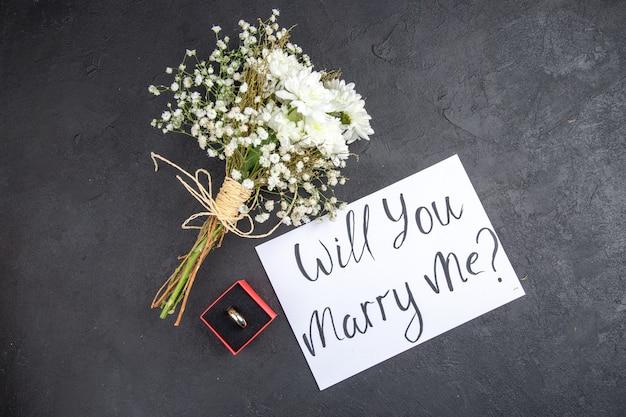 Bovenaanzicht verlovingsring in rode doos wil je met me trouwen geschreven op papieren bloemen op donkere achtergrond