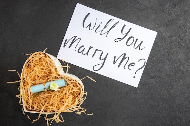 Bovenaanzicht verlovingsring scroll wens papier in hartvormige doos wil je met me trouwen geschreven op papier op donkere achtergrond
