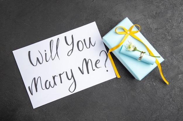 Bovenaanzicht verlovingsring scroll wens papier wil je met me trouwen geschreven op papier op donkere achtergrond