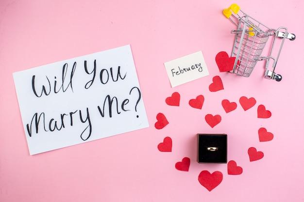 Bovenaanzicht verlovingsring wil je met me trouwen geschreven op papier rood hart stickers mini trolley op blauwe tafel