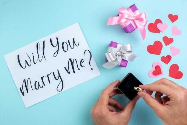 Bovenaanzicht verlovingsringdoos in mannelijke handen wil je met me trouwen geschreven op papier rode en roze harten geschenken op blauwe achtergrond