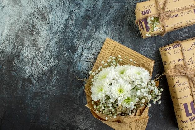 Bovenaanzicht verpakte geschenken bloemboeket op donkere achtergrond met kopieerplaats