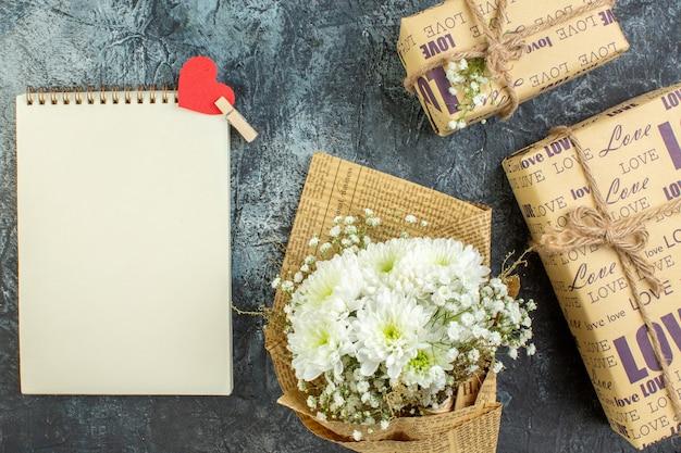 Bovenaanzicht verpakte geschenken bloemen notitieblok op donkere achtergrond