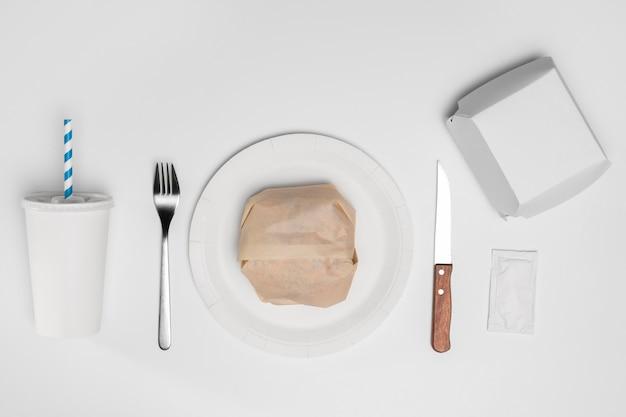 Bovenaanzicht verpakte hamburger met bestek