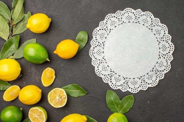 Bovenaanzicht vers citroenen zuur fruit op de donkere tafel limoen citrusvruchten