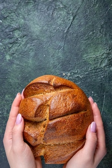 Bovenaanzicht vers donker brood met vrouwelijke handen op donker bureau