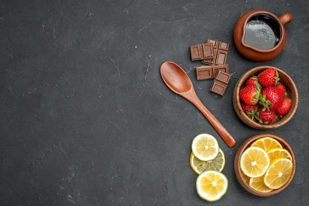 Bovenaanzicht vers fruit aardbeien en citroenen op het grijze oppervlak