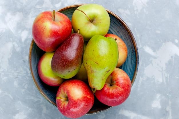 Bovenaanzicht vers fruit, appels en mango op het lichtwitte bureau