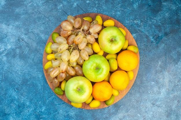 Bovenaanzicht vers fruit, appels, mandarijnen en druiven op blauwe tafel