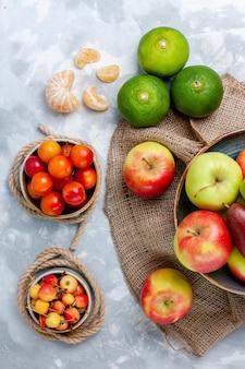 Bovenaanzicht vers fruit, appels, mandarijnen en mango op een licht wit bureau