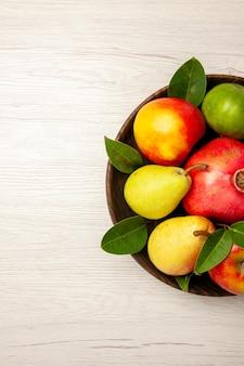 Bovenaanzicht vers fruit, appels, peren en ander fruit in de plaat op witte bureauvruchten rijpe boom zacht, veel vers