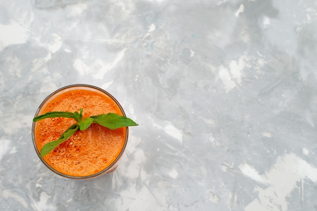 Bovenaanzicht vers fruit cocktail in lang glas met blad op grijs