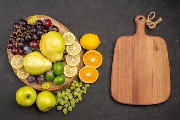 Bovenaanzicht vers fruit druiven citroen schijfjes pruimen en kweeperen op donkere ondergrond rijp vers fruit gezondheid vitamine boom