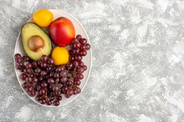 Bovenaanzicht vers fruit druiven perzik en avocado binnen plaat op wit oppervlak