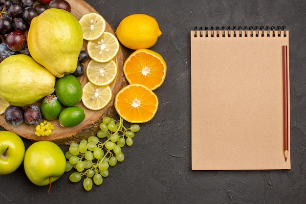 Bovenaanzicht vers fruit druiven schijfjes citroen pruimen en kweeperen op de donkere achtergrond rijp vers fruit gezondheid vitamine boom