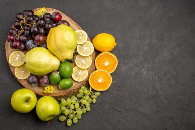 Bovenaanzicht vers fruit druiven schijfjes citroen pruimen en kweeperen op donkere ondergrond rijp vers fruit gezondheid vitamine boom