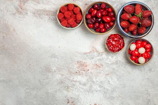 Bovenaanzicht vers fruit frambozen aardbeien en kornoeljes met koekjes op witte ruimte