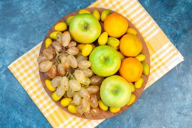 Bovenaanzicht vers fruit mandarijnen appels en druiven op blauwe tafel