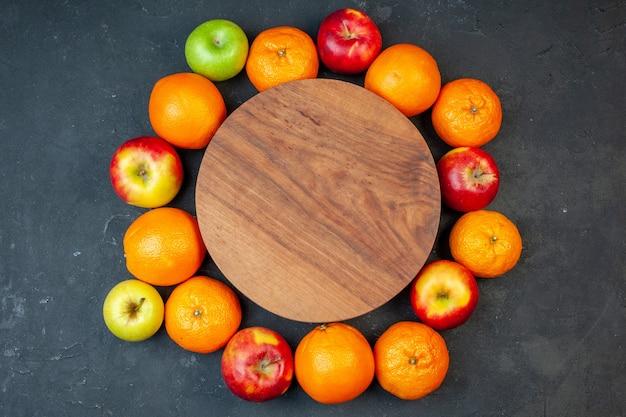 Bovenaanzicht vers fruit mandarijnen sinaasappelen bananen en appels op donkere achtergrond