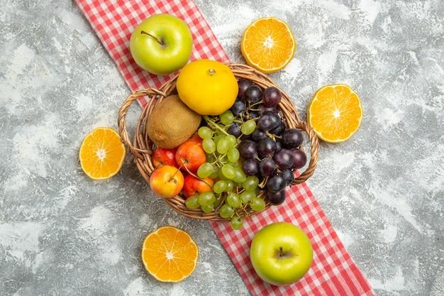 Bovenaanzicht vers fruit samenstelling druiven en pruimen met stukjes sinaasappel op witte achtergrond vitamine rijp fruit vers mellow