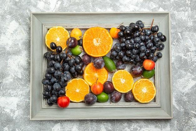 Bovenaanzicht vers fruit samenstelling druiven sinaasappels pruimen en feijoa op witte tafel