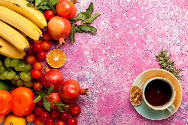 Bovenaanzicht vers fruit samenstelling met kopje thee op lichtroze bureau