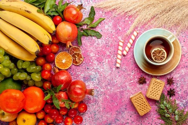 Bovenaanzicht vers fruit samenstelling met wafels en thee op lichtroze oppervlak