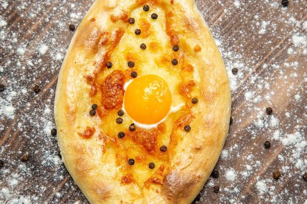 Bovenaanzicht vers gebakken brood met gekookt ei en bloem op een bruin bureau deeg bak ei brood broodje