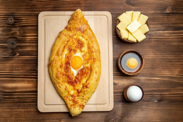 Bovenaanzicht vers gebakken brood met gekookt ei op bruin houten bureau brood deeg maaltijd broodje eten ontbijt ei