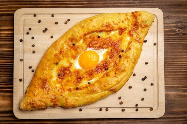 Bovenaanzicht vers gebakken brood met gekookt ei op bruin houten bureau deeg ontbijt ei broodje eten
