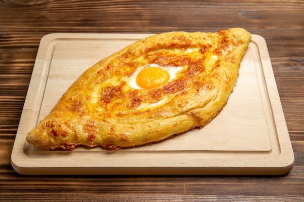 Bovenaanzicht vers gebakken brood met gekookt ei op een bruin houten bureau deeg maaltijd broodje ontbijt eivoer