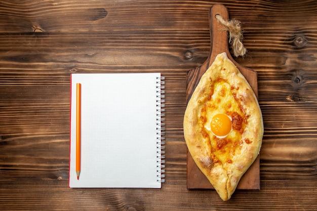 Bovenaanzicht vers gebakken brood met gekookt ei op houten bureau brood deeg broodje eten ontbijt maaltijd ei