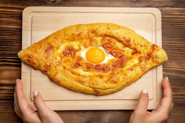 Bovenaanzicht vers gebakken brood met gekookt ei op houten bureau brood deeg maaltijd broodje eten ontbijt ei