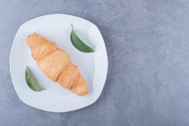 Bovenaanzicht vers gebakken franse croissant op witte plaat.