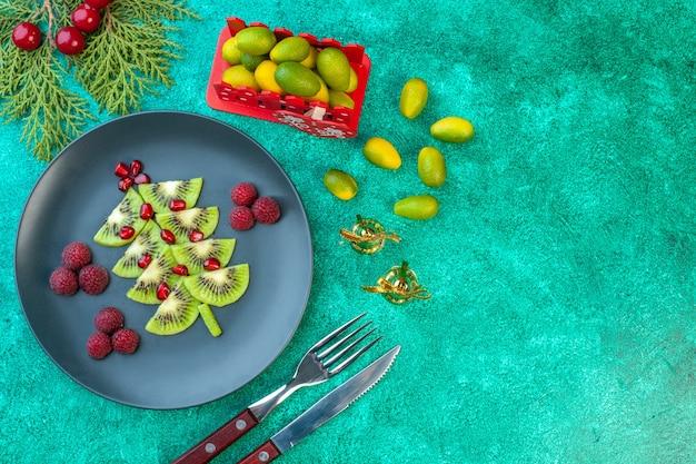 Bovenaanzicht vers gesneden kiwi's met frambozen op groene achtergrond
