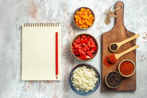 Bovenaanzicht vers gesneden kool met tomaten en peper op witruimte