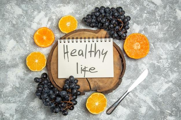 Bovenaanzicht vers gesneden sinaasappels met zwarte druiven en gezond leven schrijven op wit oppervlak citrus sap rijp vers fruit