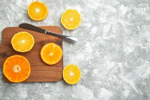 Bovenaanzicht vers gesneden sinaasappels zachte citrusvruchten op wit bureau rijp fruit exotisch vers tropisch Gratis Foto