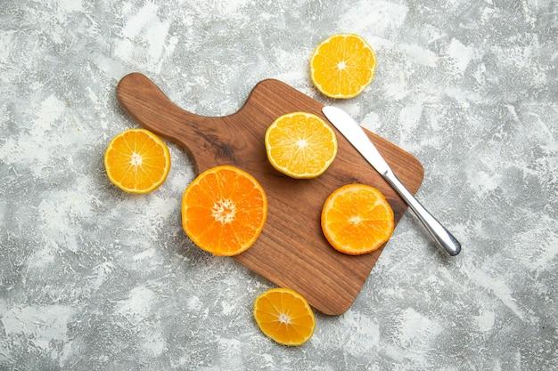 Bovenaanzicht vers gesneden sinaasappels zachte citrusvruchten op wit oppervlak rijp fruit exotisch vers tropisch