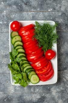 Bovenaanzicht vers gesneden tomaten elegant ontworpen salade op de grijze ruimte