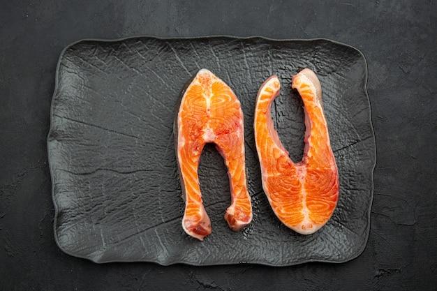 Bovenaanzicht vers vlees plakjes binnen plaat op donkere achtergrond