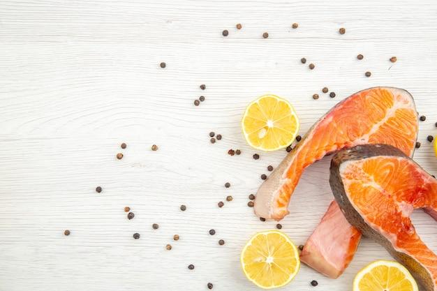 Bovenaanzicht vers vlees plakjes met schijfjes citroen op witte achtergrond